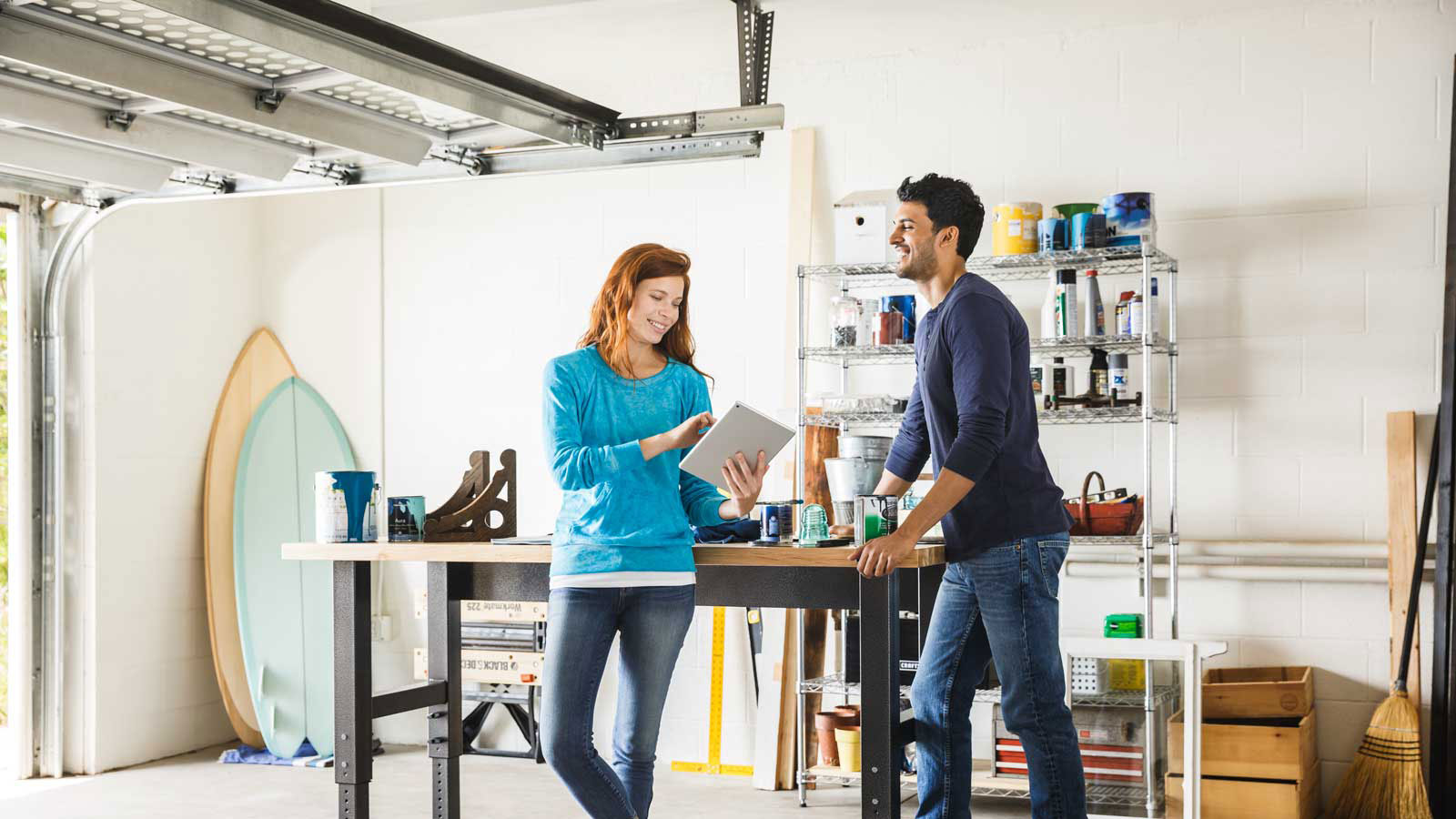 Happy man and woman talking while standing in a home garage and looking at a tablet.